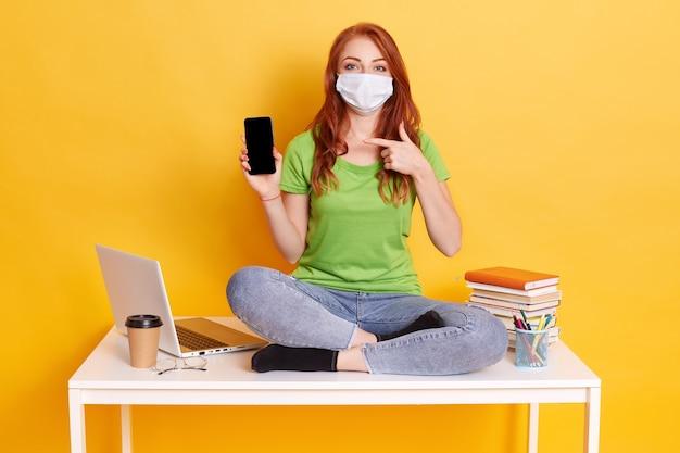Młoda rudowłosa kobieta studiuje siedząc na białym stole, trzymając telefon z pustym ekranem, otoczony książkami, kolanami, ubrana w maskę medyczną na białym tle na żółtym tle.