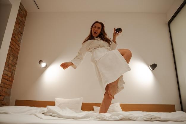 Młoda rudowłosa kobieta w ręczniku na głowie i białym szlafroku skacze i bawi się na łóżku. wesoły nastrój w pokoju hotelowym. młodzież i awanturnictwo.