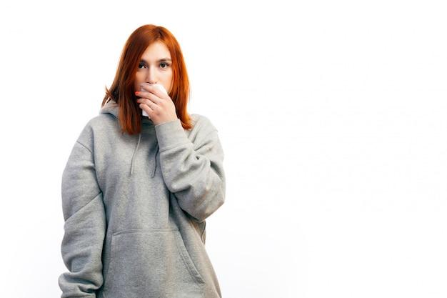 Młoda rudowłosa kobieta w szarej bluzie zachorowała na przeziębienie