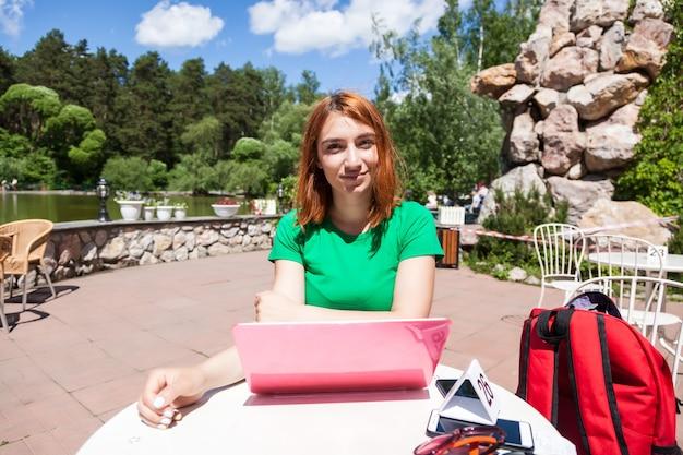 Młoda rudowłosa kobieta w zielonej koszulce uśmiecha się i siada przy stoliku w kawiarni w zoo