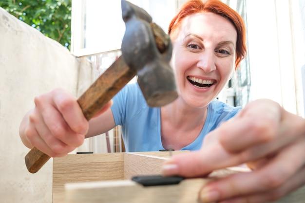 Młoda rudowłosa kobieta wbijająca się w gwóźdź i uśmiechająca się