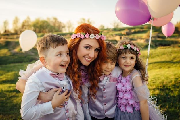 Młoda rudowłosa kobieta z dziećmi w inteligentnych ubraniach, grając z balonami w parku