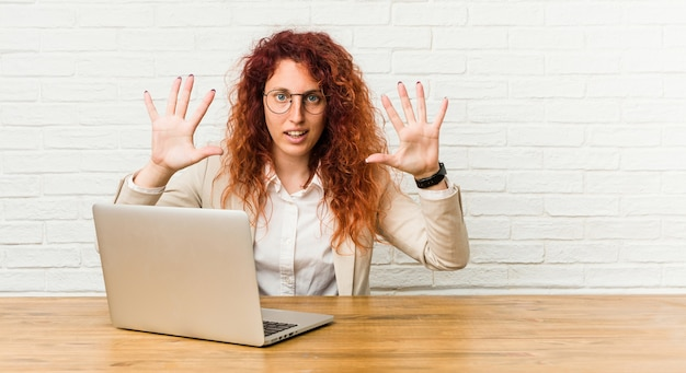 Młoda rudowłosy kręcone kobieta pracuje ze swoim laptopem pokazując numer dziesięć rękami.