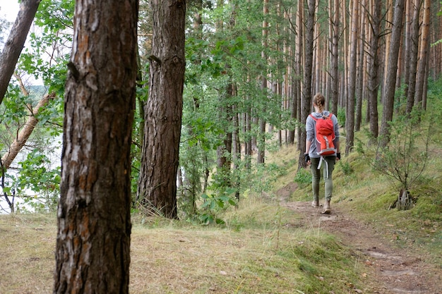 Młoda rudzielec długie włosy kobieta podróżuje w lato chmurnym lesie