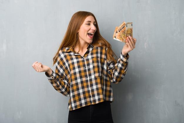 Młoda rudzielec dziewczyna nad grunge ścianą bierze dużo pieniądze