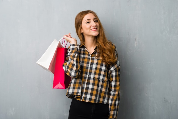 Młoda rudzielec dziewczyna nad grunge ścianą trzyma mnóstwo torba na zakupy