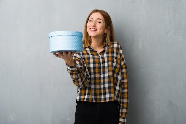 Młoda rudzielec dziewczyna nad grunge ścianą trzyma prezent w rękach