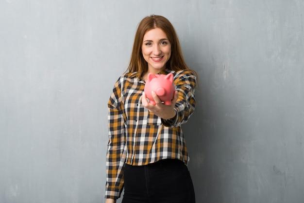 Młoda rudzielec dziewczyna nad grunge ścianą trzyma skarbonkę