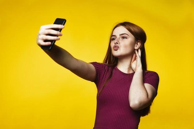 Młoda rudzielec dziewczyna robi selfie na telefonie komórkowym i wysyła lotniczego buziaka