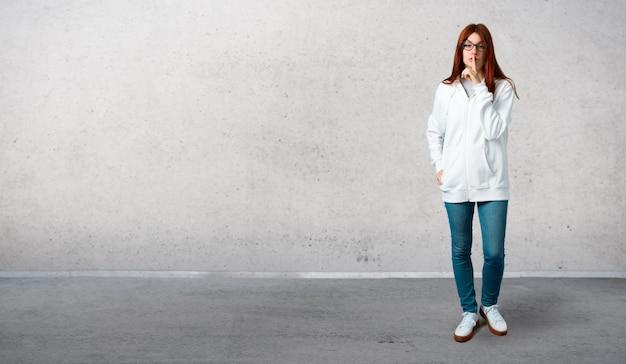 Młoda rudzielec dziewczyna w miastowej białej bluzie z szkłami pokazuje znaka