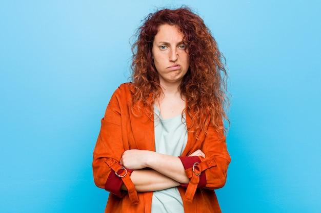 Młoda rudzielec elegancka kobieta nieszczęśliwy patrzeć z sarkastycznym wyrażeniem.