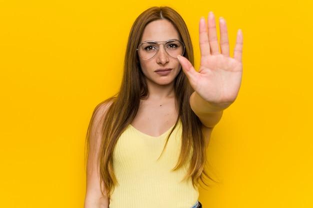 Młoda rudzielec imbirowa kobieta z piegowatą pozycją z rozpostartą ręką pokazuje znak stop, zapobieganie ci.