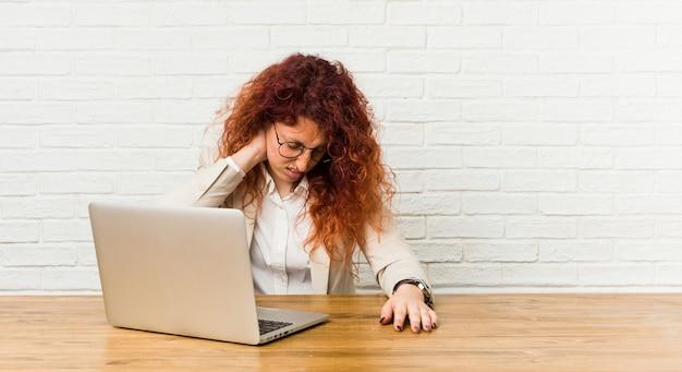 Młoda rudzielec kędzierzawa kobieta pracuje z jej laptopem cierpi ból szyi z powodu siedzącego trybu życia.