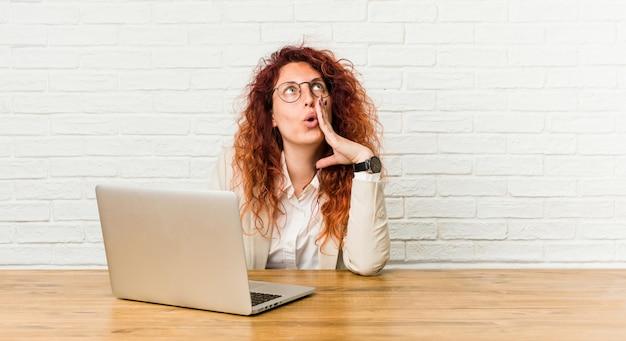Młoda rudzielec kędzierzawa kobieta pracuje z jej laptopem mówi sekretną gorącą hamującą wiadomość i patrzeje na boku