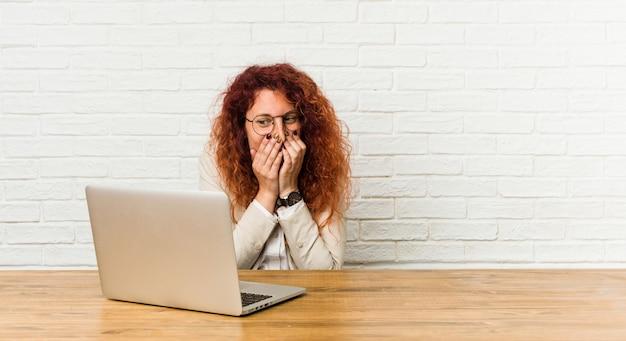 Młoda rudzielec kędzierzawa kobieta pracuje z jej laptopem śmia się o coś, zakrywający usta rękami.