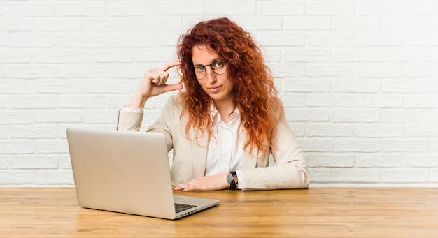 Młoda rudzielec kędzierzawa kobieta pracuje z jej laptopem trzyma coś trochę z palcami wskazującymi, uśmiechnięta i ufna.