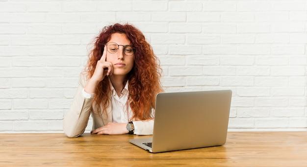 Młoda rudzielec kędzierzawa kobieta pracuje z jej laptopem wskazuje świątynię z palcem, myśleć, skupiający się na zadaniu.
