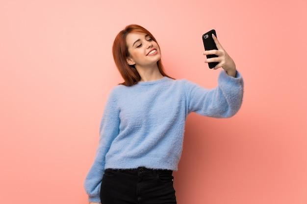 Młoda rudzielec kobieta nad menchiami robi selfie