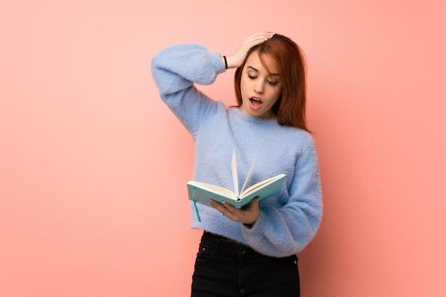 Młoda rudzielec kobieta nad menchiami zaskakującymi podczas gdy cieszący się czytający książkę