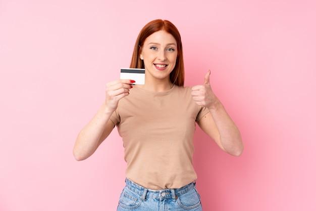 Młoda rudzielec kobieta nad odosobnionym różowym tłem trzyma kartę kredytową