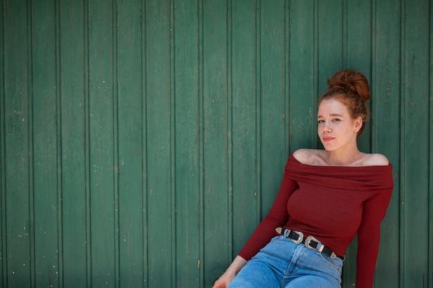 Młoda rudzielec kobieta pozuje na zielonym tle