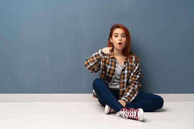 Młoda rudzielec kobieta siedzi na podłoga zaskakującej i wskazuje przód