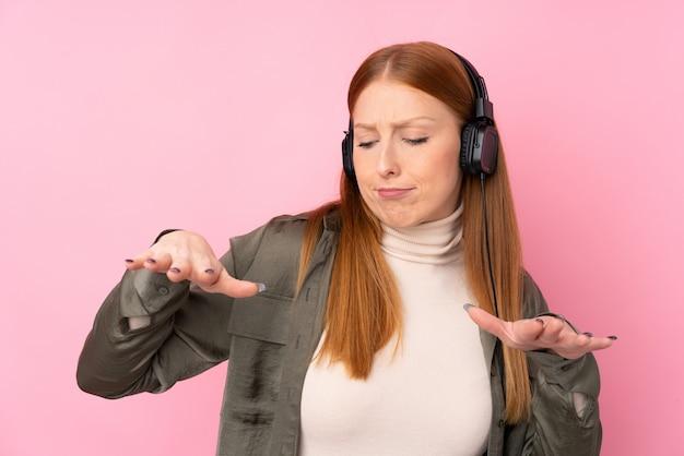 Młoda rudzielec kobieta słucha muzykę i tana