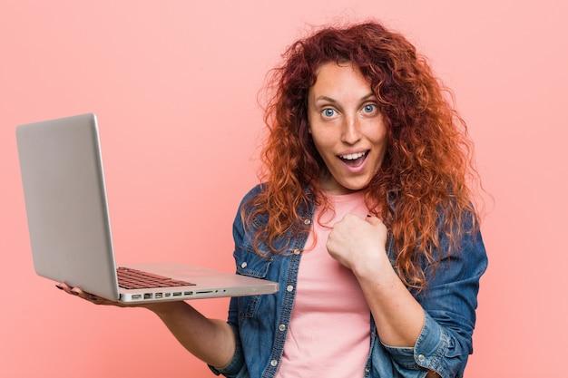 Młoda rudzielec kobieta trzyma laptop zaskakuje wskazywać na ona, ono uśmiecha się szeroko