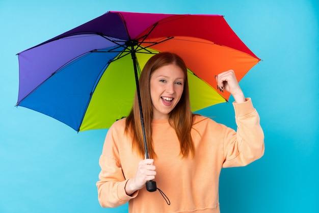 Młoda rudzielec kobieta trzyma parasol nad odosobnioną ścianą świętuje zwycięstwo