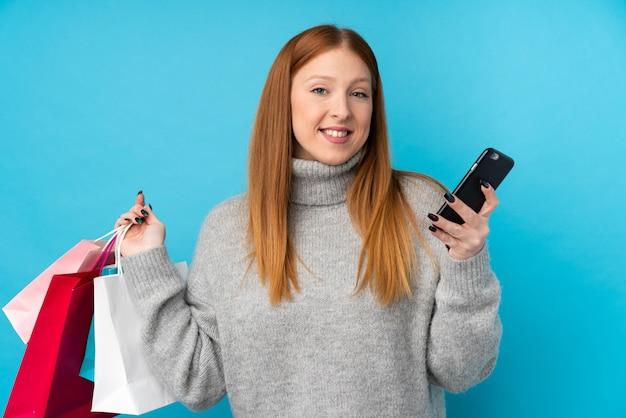 Młoda rudzielec kobieta trzyma torba na zakupy i pisze wiadomości z jej telefonem komórkowym przyjaciel