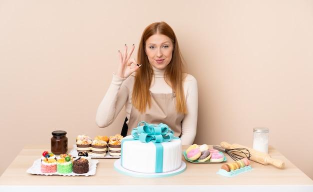 Młoda rudzielec kobieta z dużym tortem pokazuje ok znaka z palcami