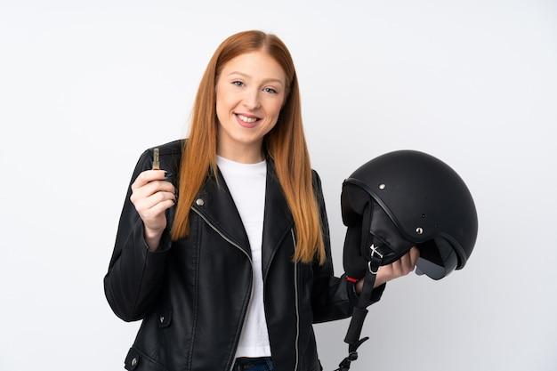 Młoda rudzielec kobieta z hełma motocyklu nad odosobnioną biel ścianą