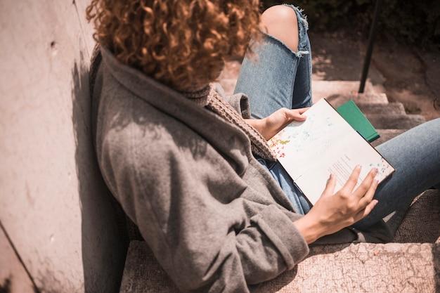 Młoda rudzielec kobieta z książką na schodku