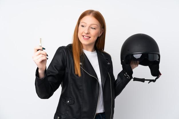 Młoda rudzielec kobieta z motocyklu hełmem nad bielem