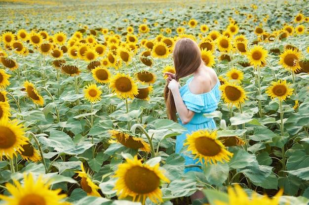 Młoda rudzielec kobieta z plecioną fryzurą w lato słonecznika polu