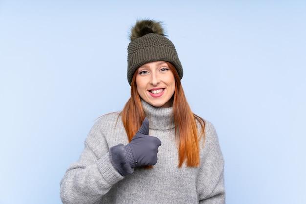 Młoda rudzielec rosyjska kobieta z zima kapeluszem nad odosobnioną błękit ścianą daje aprobata gestowi