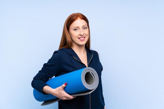 Młoda rudzielec sporta kobieta nad odosobnionym błękitnym tłem z ono uśmiecha się i matą