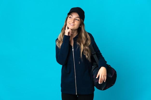 Młoda rumuńska kobieta sport z torbą sportową na białym tle na niebieskiej ścianie myśli pomysł, patrząc w górę