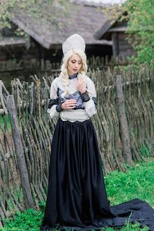 Młoda samica o wyglądzie słowiańskim w koronie, kokoshnik nad latem letnim, wieś, zagroda