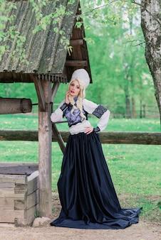 Młoda samica o wyglądzie słowiańskim z koroną, kokoshnik w przesilenie letnie, wieś, zagroda