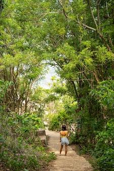 Młoda samica stoi pod tropikalnymi drzewami