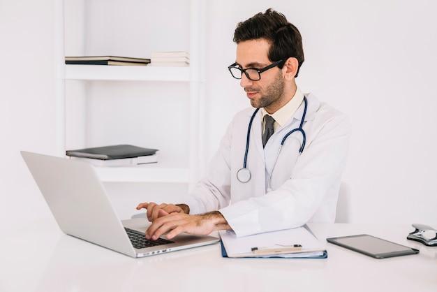 Młoda samiec lekarka jest ubranym eyeglasses używać laptop w klinice