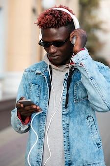 Młoda samiec na ulicznej słuchającej muzyce