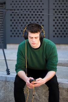 Młoda samiec z hełmofonami słucha muzyka