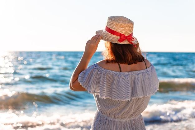 Młoda samotna kaukaska rudowłosa dziewczyna w słomkowym kapeluszu i letniej sukience z powrotem na plaży w pobliżu morza i wygląda