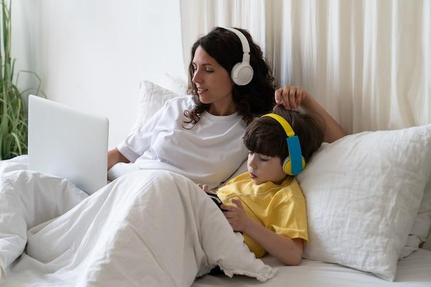 Młoda samotna matka decyduje się pracować zdalnie z domowego biura, aby spędzać więcej czasu z małym chłopcem. mama i dziecko leżą w łóżku zajęci pracą niezależną online i e-learningiem edukacji przedszkolnej na odległość