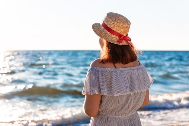 Młoda samotna rudowłosa kaukaska dziewczyna w słomkowym kapeluszu i letniej sukience z powrotem na plaży w pobliżu morza