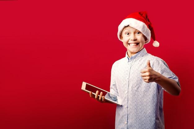 Młoda santa chłopiec robi ok aprobatom gestykuluje podczas gdy trzymający pastylkę