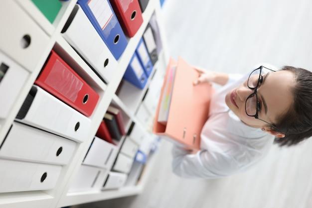 Młoda sekretarka w okularach bierze teczkę z dokumentami z półki w archiwum