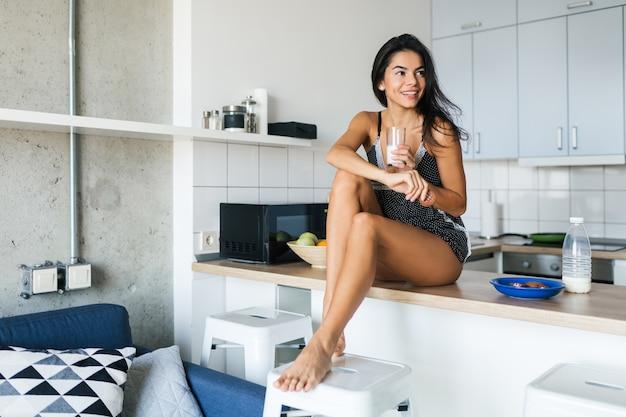 Młoda seksowna atrakcyjna kobieta rano siedzi w kuchni jedząc zdrowe śniadanie, pijąc mleko ze szkła, chude nogi, brunetki, uśmiechając się